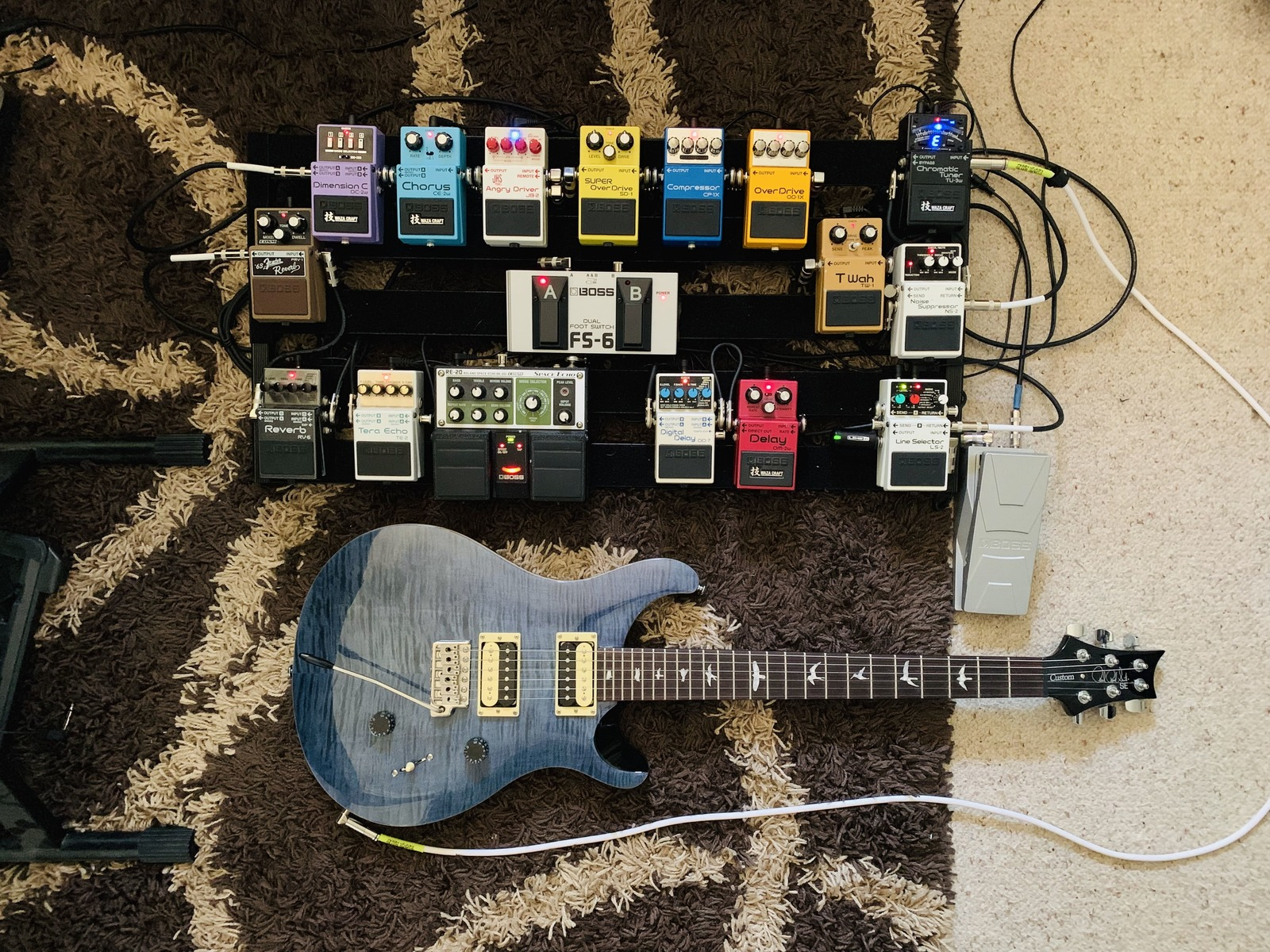 Photo of Boss LS-2 Line Selector and more gear in a pedalboard and guitar